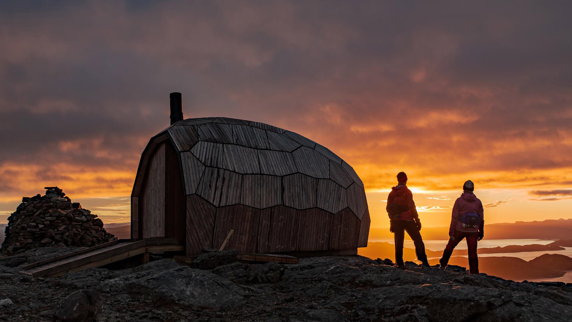 Günbatımında ayakta duran iki kişi ile birlikte ahşap kabin
