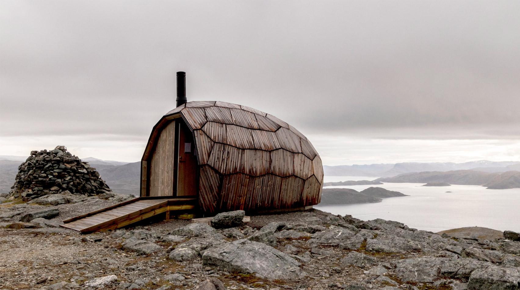 Dağ ve göl manzarasında ahşap kabin dış görünüşü